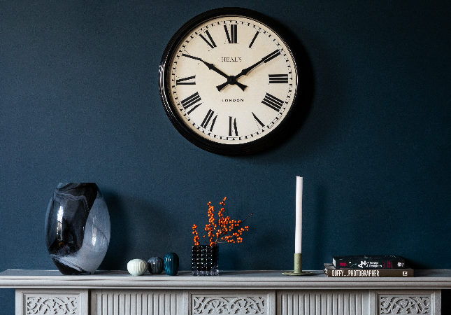 A Heal's analogue clock over a carefully styled mantelpiece
