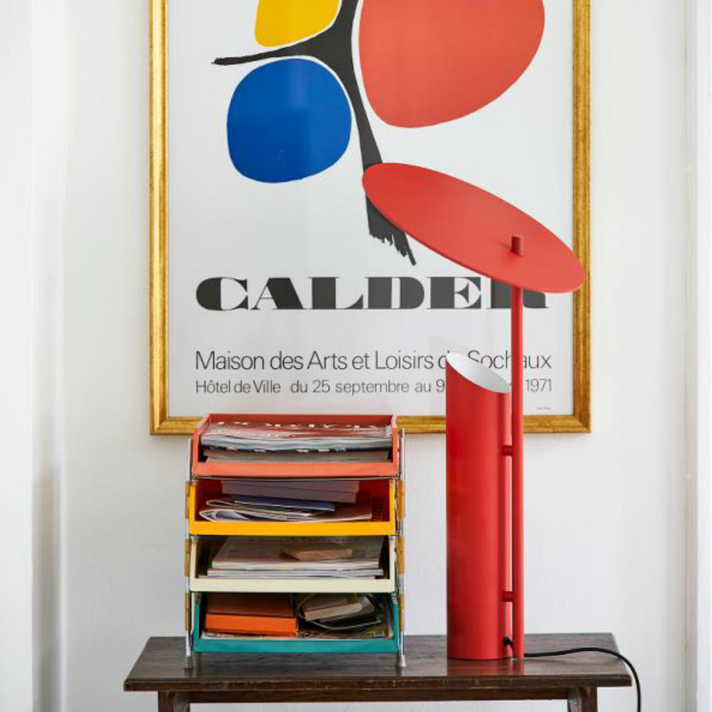 The red Reflect Table Lamp in front of an Alexander Calder poster