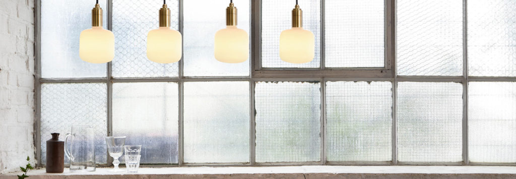 Four of Tala's sustainable light bulbs hanging in front of a window