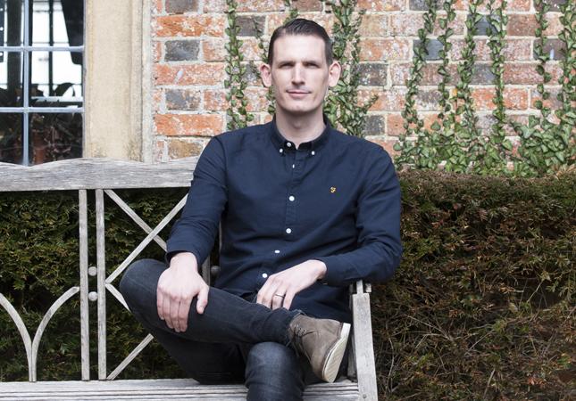 A portrait of Rob Scarlett sat outside
