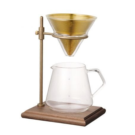 Brewer set includes walnut base with brass and glass stand to hold the brass filter as well as the glass coffee pot